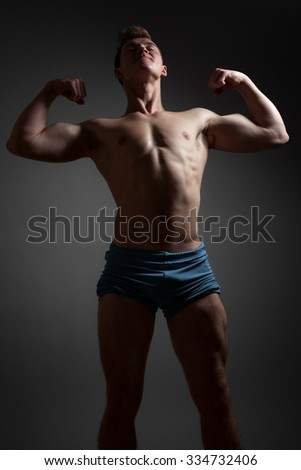 Athletic young man shows muscles