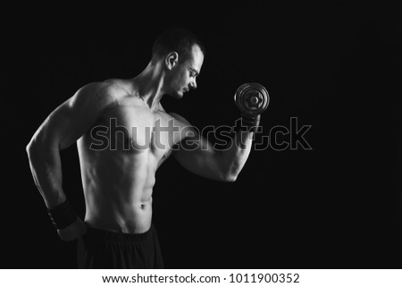 Athletic young man with dumbbell on a black background. Naked torso, muscular body. Strong chest and shoulder muscles. Studio shot, low key. Bodybuilding concept, copy space, black and white image