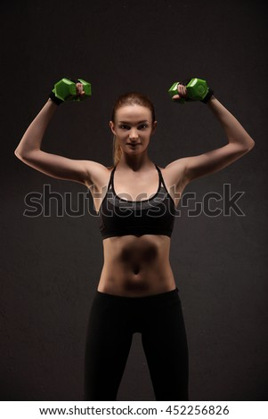 Athletic young woman doing a fitness workout with weights. Fitness girl workout dumbbells on smoke dark background doing shoulder exercises