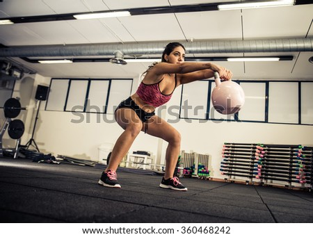 Athletic young woman doing squat exercises for the buttocks - Fitness model working out in a gym - Pretty young woman training to stay fit and healthy - stock photo