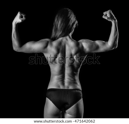 Athletic young woman flexing her back and arm muscles