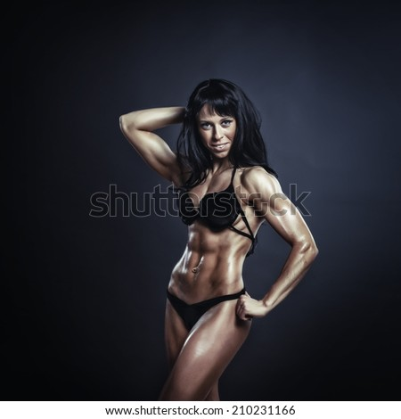 athletic young woman posing and doing a fitness workout with dumbbells on black studio background