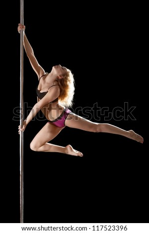 Athletic young woman show pole dance element
