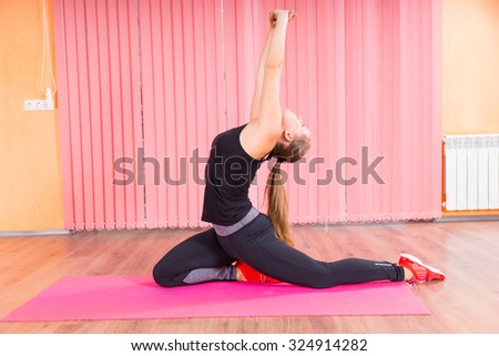 Athletic Young Woman Stretching her Arms, Back and Legs While Kneeling on a Pink Mat inside a Fitness Studio. - stock photo