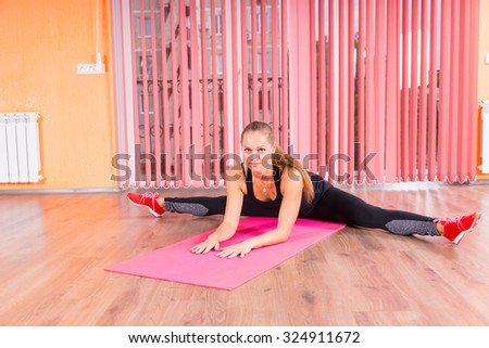 Athletic Young Woman Stretching her Legs on the Sides on Top of a Fitness Mat and Looking at the Camera. - stock photo