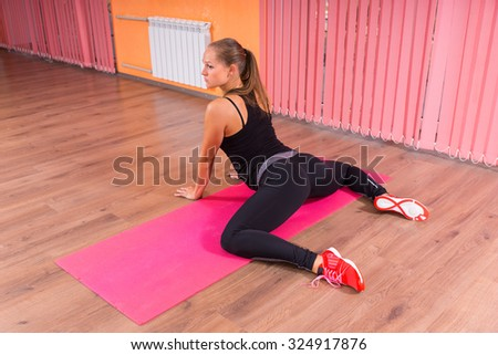 Athletic Young Woman Stretching her Legs While Leaning on the Floor Inside the Fitness Studio. - stock photo