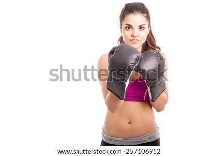 Athletic young woman wearing boxing gloves looking fearless with plenty of copy space - stock photo