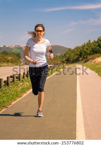 Athletic young woman with earphones listening music from her smartphone while running on a runway outdoors. Modern healthy lifestyle concept. - stock photo