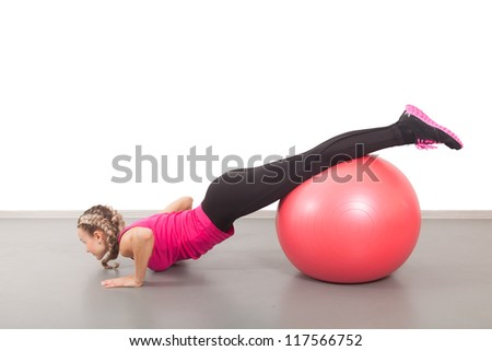 Athletic young woman with red ball on the floor