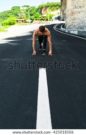 Athletics. Athletic Man With Fit Muscular Body In Starting Position For Running On Road. Handsome Runner Ready To Start Sprint Race. Fitness Model Training Outdoors In Summer. Sports Workout Concept