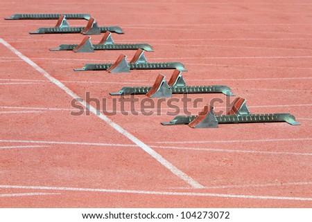 Athletics Starting Blocks on a red running track in the stadium. - stock photo