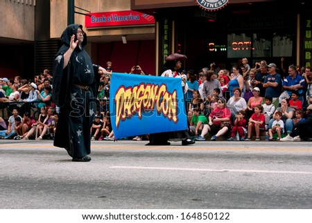 ATLANTA, GA - AUGUST 31:  A crowd of spectators lines Peachtree Street in downtown Atlanta as the start of the Dragon Con parade passes by on August 31, 2013 in Atlanta, GA.   - stock photo