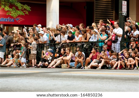 ATLANTA, GA - AUGUST 31:  A large crowd of spectators lines Peachtree Street in downtown Atlanta and takes pictures as the annual Dragon Con parade passes by, on August 31, 2013 in Atlanta, GA.  - stock photo