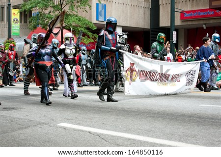 ATLANTA, GA - AUGUST 31:  Mandalorian mercenaries from the Star Wars movies walk down Peachtree Street in the annual Dragon Con parade, on August 31, 2013 in Atlanta, GA.   - stock photo