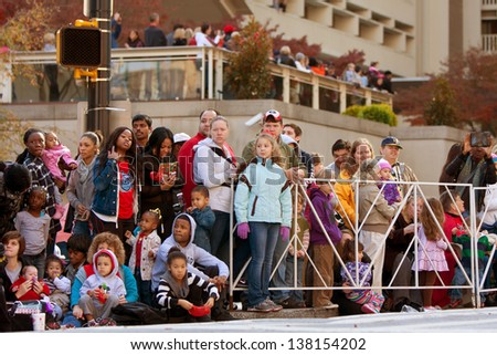 ATLANTA, GA - DECEMBER 1:  Spectators watch from the curb as the Atlanta Christmas parade takes place on Peachtree Street on December 1, 2012, in Atlanta, GA. Thousands of spectators attended. - stock photo