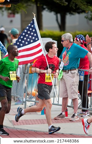ATLANTA, GA - JULY 4:  A runner carries a large American flag to celebrate Independence Day while running toward the finish line of the Peachtree Road Race on July 4, 2014 in Atlanta, GA.  - stock photo