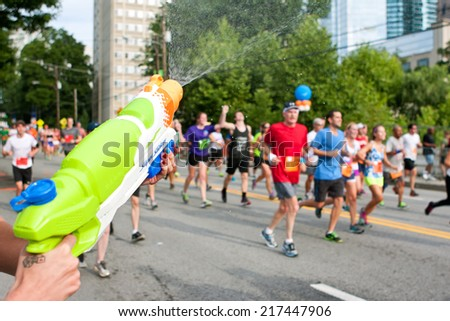 ATLANTA, GA - JULY 4: A woman soaks tired runners with a squirt gun as they head toward the finish line of the Peachtree Road Race on July 4, 2014 in Atlanta, GA.  - stock photo