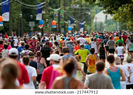 ATLANTA, GA - JULY 4:  Thousands of runners crowd an Atlanta street on their way to the finish line of the Peachtree Road Race, on July 4, 2014 in Atlanta, GA.  - stock photo