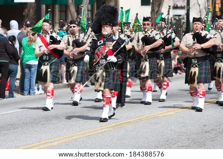 ATLANTA, GA - MARCH 15:  A bagpipes corps performs while walking in the annual St. Patrick's parade on Peachtree Street, on March 15, 2014 in Atlanta, GA.  - stock photo