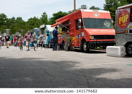 ATLANTA, GA - MAY 25:  Patrons buy food from mobile food trucks at the GREAT festival, an event celebrating Great Britain and the United Kingdom, on May 25, 2013 in Atlanta, GA.
