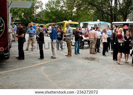 "ATLANTA, GA - OCTOBER 16:  Customers stand in line to order meals from several food trucks during their lunch hour, at ""Food Truck Thursday"" on October 16, 2014 in Atlanta. - stock photo"