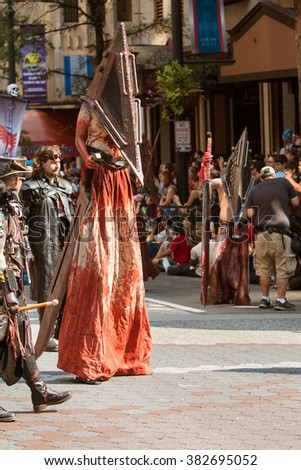 ATLANTA, GA - SEPTEMBER 5:  A man on stilts wears a scary bloodstained costume as he walks in the annual Dragon Con parade on September 5, 2015 in Atlanta, GA.  - stock photo