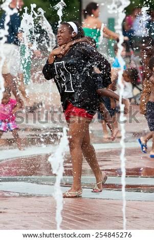 ATLANTA, GA - SEPTEMBER 6:  A mother gets soaked carrying her child piggyback through the Centennial Park fountain on September 6, 2014 in Atlanta, GA.  - stock photo