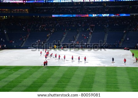 ATLANTA, GEORGIA - JUNE 16: Stadium workers place plastic on the field as rain caused delays during a Braves vs. Mets game at Turner Field on June 16, 2011 in Atlanta, Georgia. - stock photo