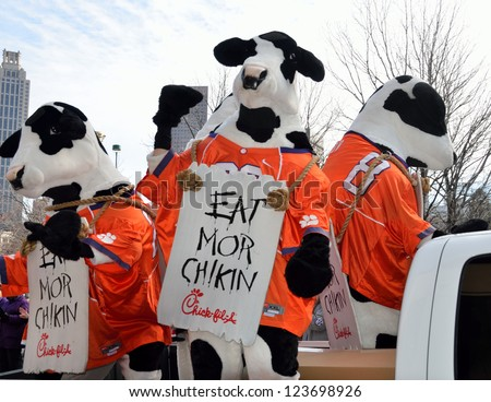 ATLANTA, GEORGIA, USA - DECEMBER 31:  Famous ' Eat Mor Chikin ' cows at parade leading up to the Chick-fil-A bowl game. Event took place at the Georgia Dome with Clemson and LSU on December 31, 2012. - stock photo