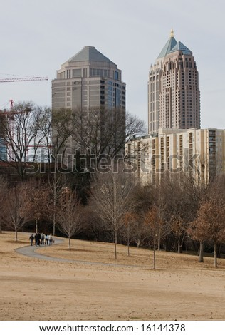 Atlanta's Midtown skyline in Winter as seen from a park setting.  Walkers seen on path - stock photo