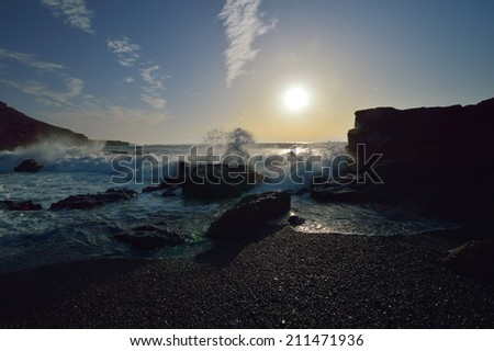 Atlantic Ocean coast with black beach near Charco de los Clicos, Lanzarote, Canary Islands. Romantic shore with waves splash on the rocks in the evening. - stock photo