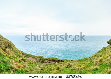 Atlantic ocean overcast sky and field of green grass, Ireland Europe - stock photo