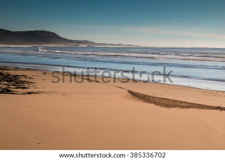 Atlantic Ocean shore in Morocco Sandy beach at the Atlantic Ocean shore in Morocco. Small waves of the ocean. Mountain in the background. Early evening little cloudy sky.  - stock photo