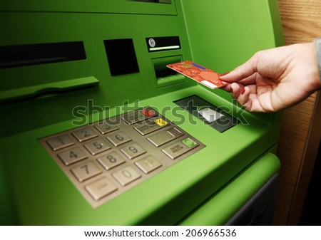 ATM and hand with card. - stock photo