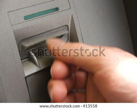 ATM transaction - hand blurry, machine in focus - stock photo