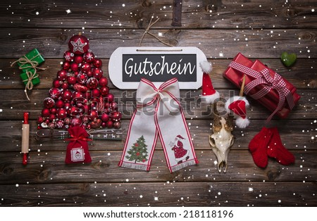 Atmospheric christmas decoration in red with german text - gift certificate. Business idea for presents and gifts. - stock photo
