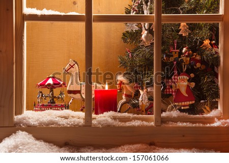 Atmospheric Christmas window sill decoration:snow,tree,candle,rocking horse and carousel - stock photo