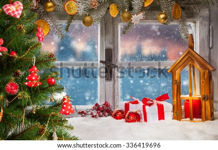 Atmospheric Christmas window sill decoration with beautiful sunset view. Christmas tree on foreground - stock photo