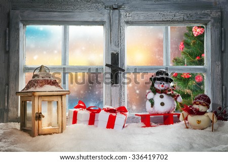 Atmospheric Christmas window sill decoration with beautiful sunset view. Christmas tree on background - stock photo