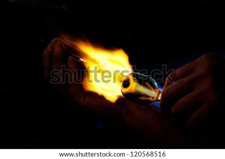 Atmospheric image of glass being molten and shaped over a bunsen burner - stock photo