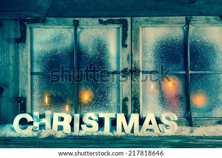 Atmospheric old christmas window with red candles and text. - stock photo