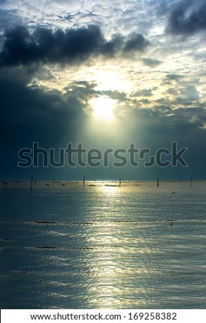 Atmospheric sunrise behind storm clouds showing bright colorful sunrays - stock photo