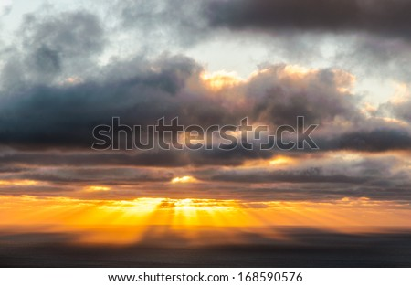 Atmospheric sunset behind storm clouds showing bright colorful sunrays - stock photo