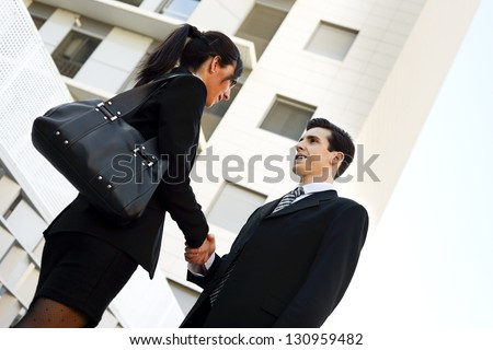 Atractive businessman and businesswoman shaking hands outside of office building. Couple working. - stock photo