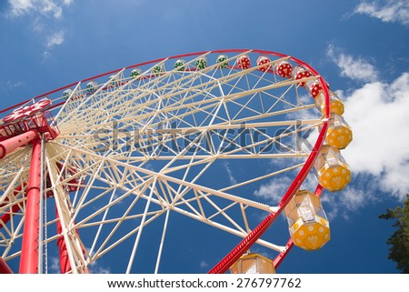 Atraktsion Ferris wheel against a blue sky with clouds