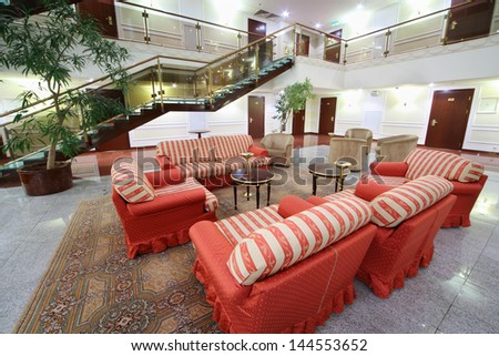 Atrium with red soft armchairs, couches and stairs in stylish hotel. - stock photo