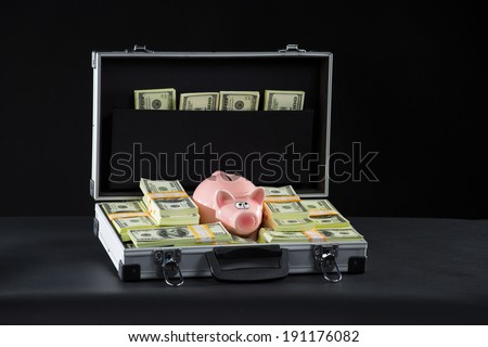 Attache full of money. A classic type suitcase full of 100$ bills money packs pink Piggy bank - stock photo