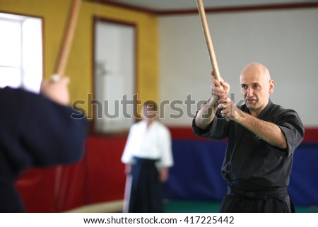 Attack and defense; men practicing sword technique - stock photo