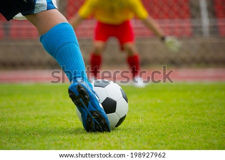 Attack soccer player shooting to defense team in football stadium. - stock photo