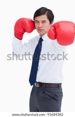 Attacking fist of tradesman in boxing glove against a white background